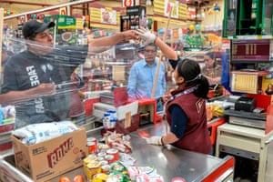 A cashier in Toluca, Mexico, serves customer behind a makeshift plastic curtain as a preventive measure against the spread of the coronavirus