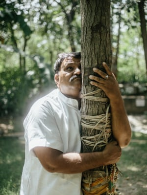 Shyam Sunder Paliwal hugs the burflower tree planted in remembrance of his daughter.