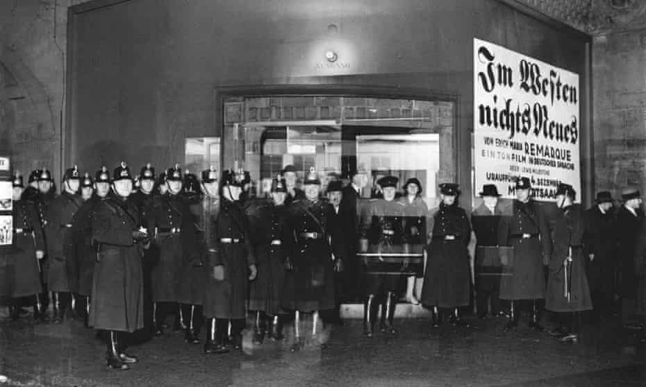 A large group of uniformed police officers, some smiling at the camera, in a cinema lobby with a sign behind them that says Im Western Nichts Neues)