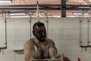 A miner smokes a cigar while showering at the end of his workday in Mieres, Spain.