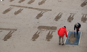 Volunteers create beach drawings as part of Danny Boyle's the Pages of the Sea remembrance project