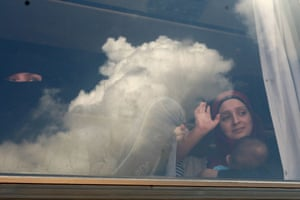 Syrian refugees wave through the windows of a bus as they prepare to leave the Lebanese capital Beirut to return to their homes in Syria.