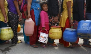 A girl stands in a queue to fill her container with water near the makeshift shelters