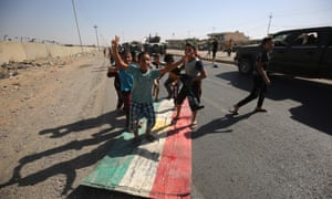 Iraqi children step on a Kurdish flag as forces advance towards the centre of Kirkuk during an operation against Kurdish fighters on Monday.