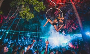 A performer hoists themselves onto a metal ring above a crowd of partygoers at Day Zero Festival, Tulum, Mexico.