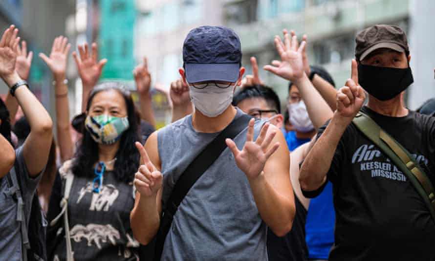 Demonstrators make a 'five demands, not one less' gesture at a protest against Chinese influence in Hong Kong.