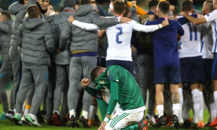 Northern Ireland's Kyle Lafferty sinks to his knees as the Slovakia players celebrate the play-off win which qualifies them for Euro 2020.
