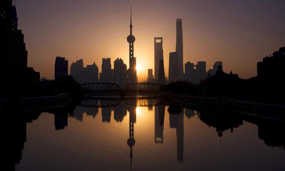 The sun rises behind the skyline of Shanghai in the Lujiazui Financial District of Pudong
