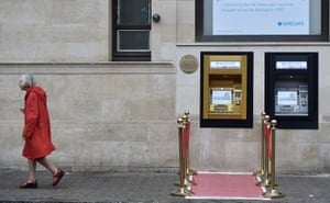 Enfield, England: A woman walks past a golden ATM, marking the location of the first cash machine 50 years ago