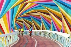 Qingdao, China. Cyclists cross a colourful footbridge in a park in Shandong province