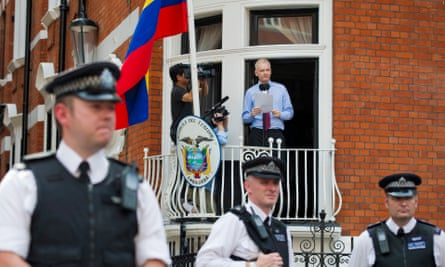 WikiLeaks founder Julian Assange speaks from the Ecuadorian embassy in London in August 2012 as police officers stand guard.