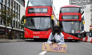 A protester sits in the road blocking the traffic as people gather in Westbourne Park for the inaugural Million People March from Notting Hill to Hyde Park in London on 30 August.