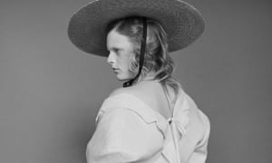 Hanne Gaby Odiele in an oversized white jacket showing her back and a shoulder and a wide-brimmed straw hat.