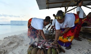 Locals cook fish on an umu, or traditional earth oven, by the lagoon in Funafuti. Groups across the island helped feed the delegates during the foruem.