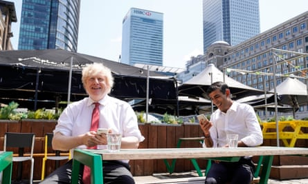 Boris Johnson and Rishi Sunak smiling an an outdoor restaurant table, looking at their phones, with the towers of Canary Wharf in the background