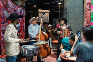 Two young men enjoy a hired mariachi band playing them music while they have a late night dinner. It is the only small restaurant that remains open on Plaza Garibaldi since the pandemic restrictions have come in place.