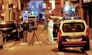 A forensic officer and a police officer stand next to a numbered reference index pad and a camera on a tripod near the scene of the crime in Paris.