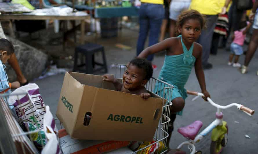Children wait for their mother at a street market in the favela complex of Maré, Rio de Janeiro.