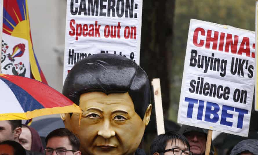Supporters of Falun Gong, including one wearing a large mask with the likeness of Xi Jinping, protest outside Downing Street.