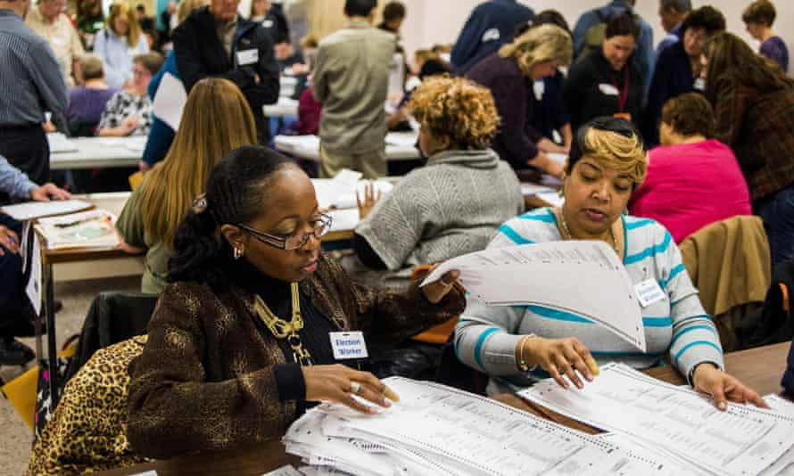 Election workers recount votes as they begin the process of a statewide recount on Wednesday, before a judge's ruling effectively ended it.
