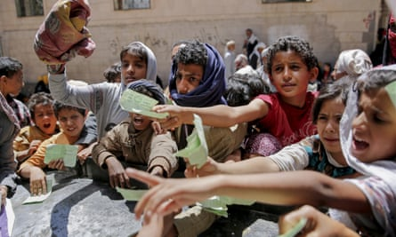 Yemeni children present documents to receive food rations provided by a local charity in Sana'a, Yemen