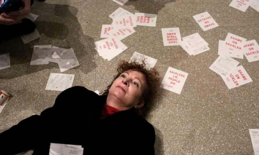 Nan Goldin lies on the floor of the Guggenheim Museum, surrounded by leaflets