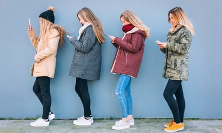 Four young women standing in a row using their cell phones