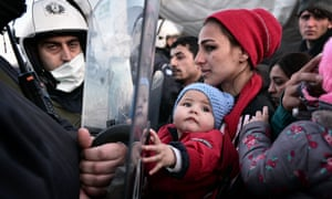 A woman holds a baby as migrants and refugees stand facing police while waiting to cross into Macedonia.