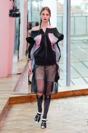 A luxe, off-shoulder bomber jacket worn over a transparent skirt mixes modernity with femininity.