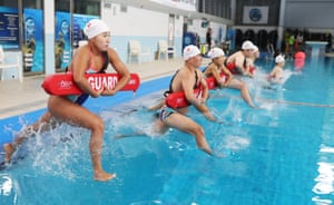 Suwon, South Korea. Lifeguards from a branch of the National Red Cross enter a pool to rescue a simulated drowning swimmer in Suwon, south of Seoul, as they take part in a rescue drill to get ready for the summer season