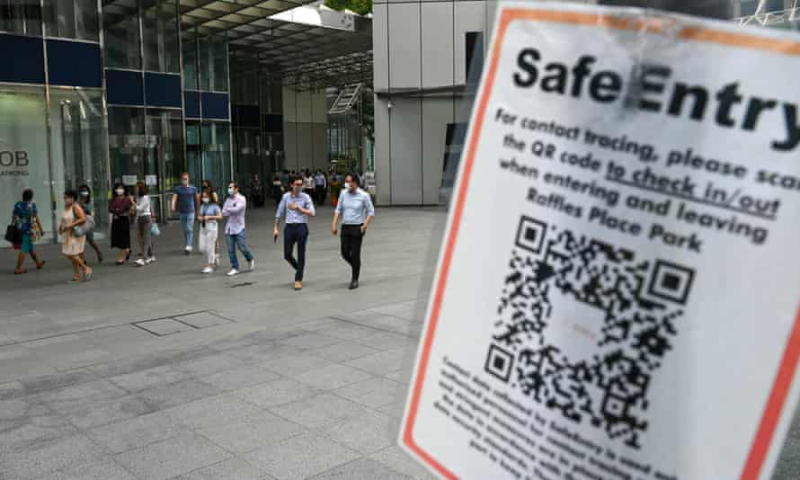 A Covid-19 coronavirus contact tracing sign is pictured as people walk out during lunch break at the Raffles Place financial business district in Singapore on Tuesday.