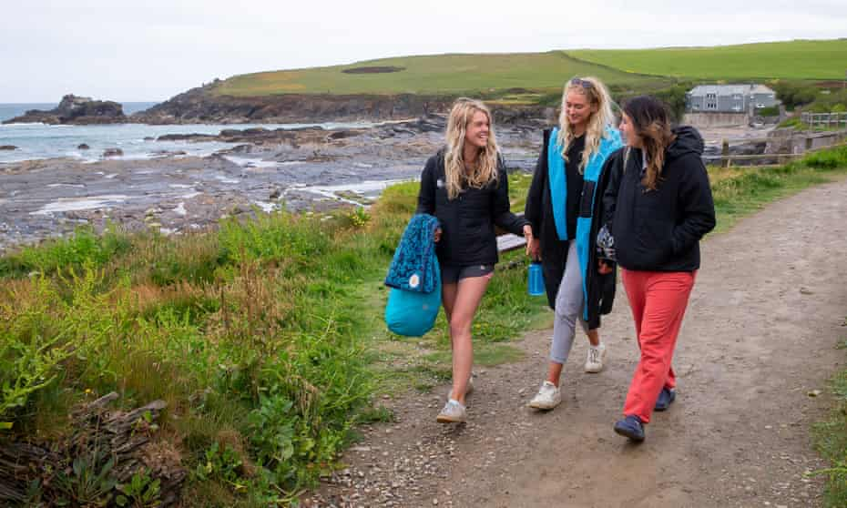 The three friends walking on a path beside the sea