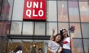 Women take a selfie outside the Uniqlo flagship store in Beijing.