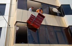 Residents evacuate their belongings from their damaged apartment building, in Pedernales