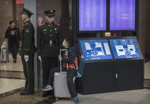 A boy talks to a paramilitary police officer as he waits at Beijing railway station