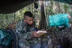 A Farc guerrilla known as Dario passes the time by reading a book of Colombian history