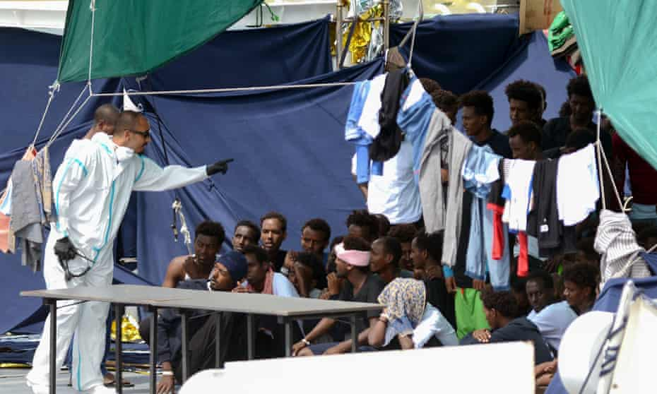 An official gestures towards migrants on the deck of the Diciotti in the port of Catania