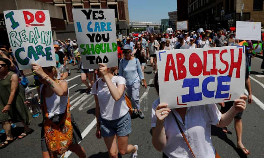 A demonstrator carries a sign reading 'Abolish Ice' at a 'Families Belong Together' rally in Boston on 30 June.
