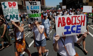 Demonstrators carrying 'Abolish ICE' and 'I Really Do Care' signs during the 'Families Belong Together' rally in Boston, Massachusetts, on 30 June 2018.