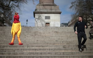 A man jogs past a person in a chicken costume in London, England