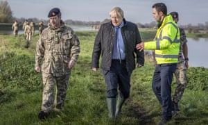 Boris Johnson walks with Lt Col Tom Robinson from the Light Dragoons and Oliver Harmar, Yorkshire area director of the Environment Agency, during a visit to Stainforth.