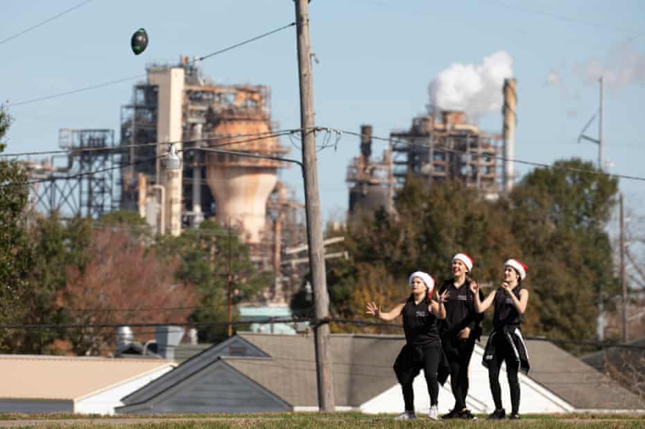 Girls playing football on the levee in Norco. Louisiana before the start of the 2019 Norco Civic Association Christmas Parade. Shell's petrochemical Norco complex looming in the background.