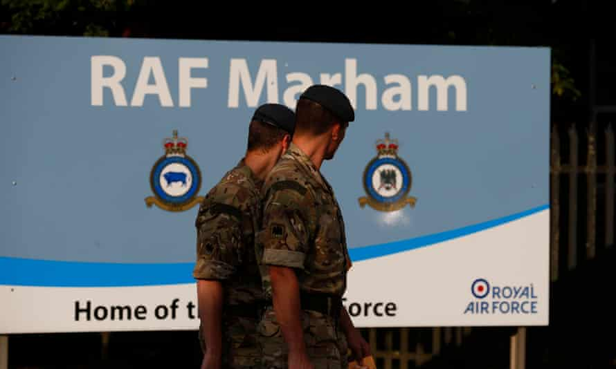 Servicemen walk past a sign at the entrance of RAF Marham in Norfolk