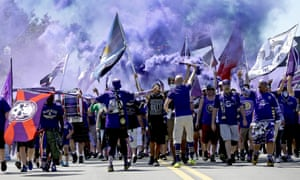 Orlando City fans march to a game against the New York Red Bulls earlier this season