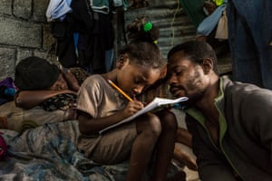 Jean Michelle (pictured right), 35, helps his 7-year-old daughter Fatdjoulie with her homework, while Catrine Telamoure, who lives with Jean and his three children, takes a nap