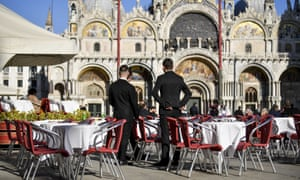Waiters stand by empty tables in a cafe in St Mark's Square in Venice