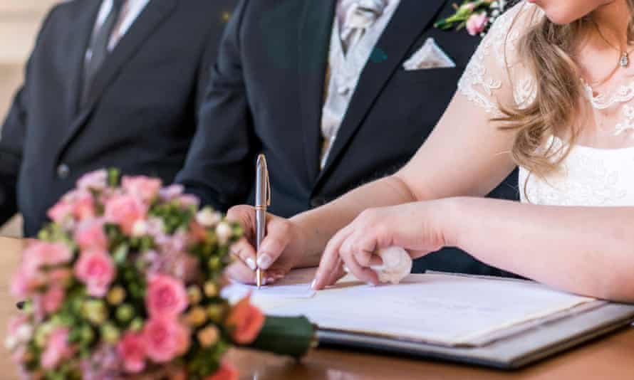 A couple signing a marriage register.