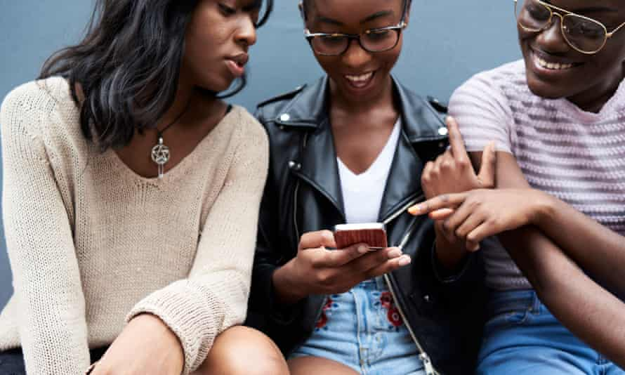 Three friends looking at a mobile phone screen