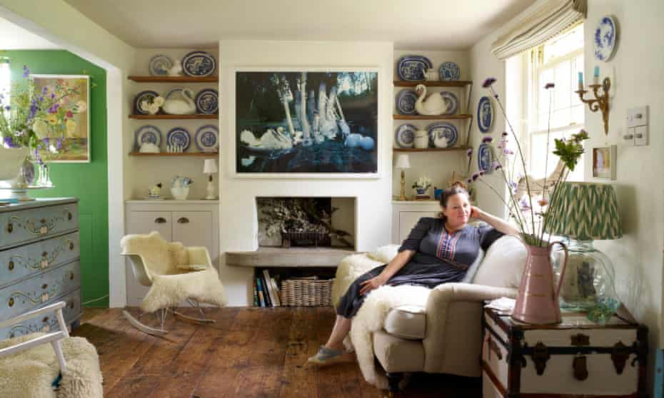 Tamsin Scott in her sitting room with a picture with swans in it above the fireplace and swan vases and blue and white crockery on the shelves