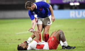 France's fly-half Camille Lopez consoles Tonga's full back Telusa Veainu after France win 23-21.
